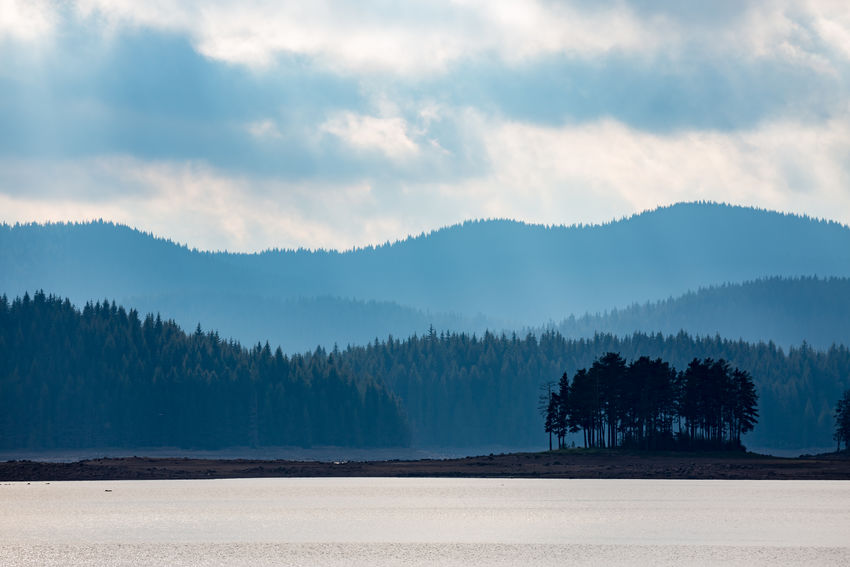 Small natural island with pine trees and layered mountain hills background. Moody colorful image with overwhelming blue color at Shiroka Polyana lake, Bulgaria, Rhodope mountain Bulgarian Nature Natural Pine Pine Forest Pine Forests Shiroka Polyana Bulgaria Clouds Island Isle Lake Lake View The Traveler - 2018 EyeEm Awards