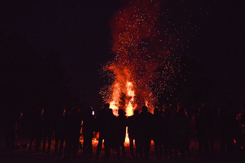 Rear view of silhouette people standing by fire