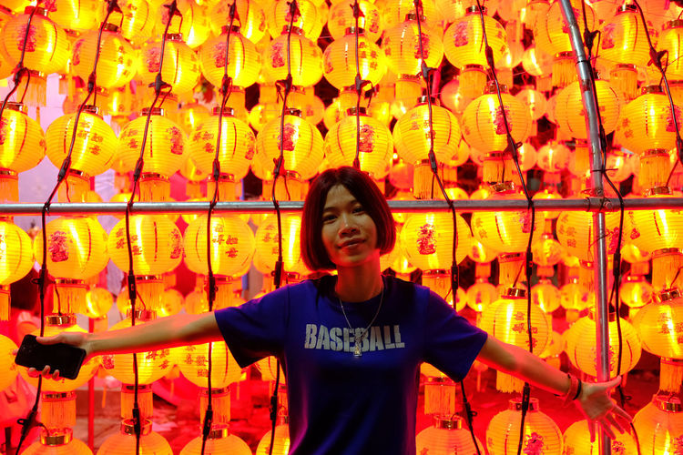 Portrait of young woman standing against chinese lanterns at night