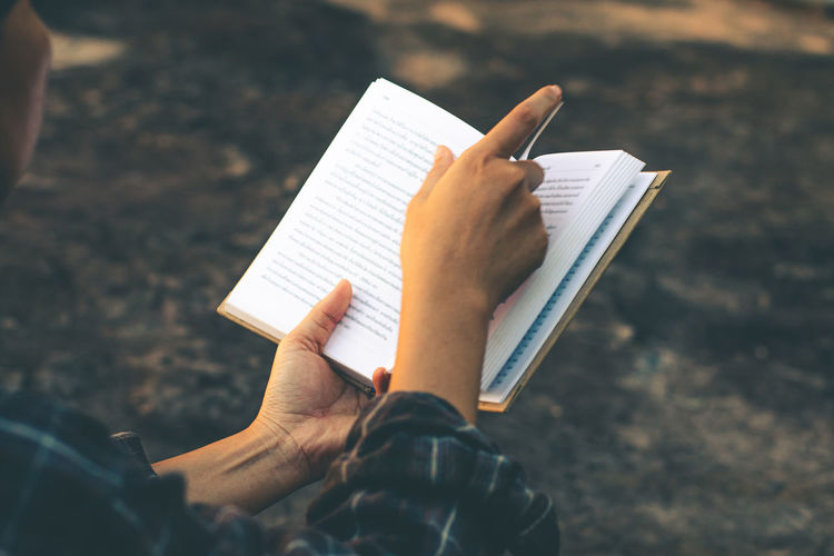 Low section of person holding book against paper