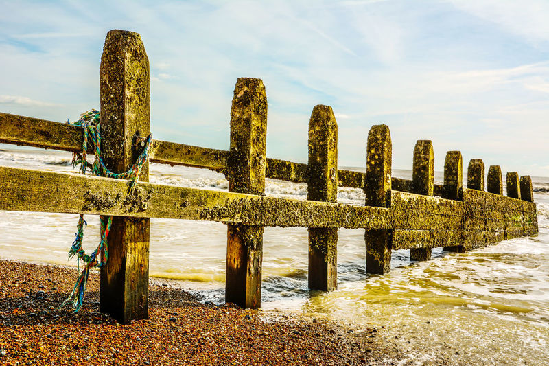 Wooden posts on beach against sky