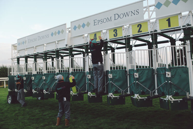 Casual Clothing Contest Day Epsom Downs Racecourse Event Full Length Gates Holding Horse Horse Race Horse Racing Jockey Jockeys Lifestyles Men Outdoors Race Course Racecourse Riding Speed Standing Start Text Western Script Focus On The Story