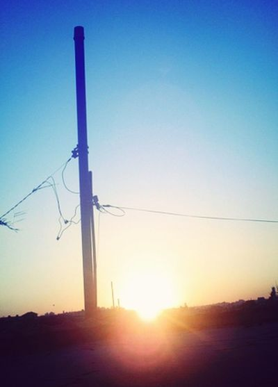 Power lines against sky at sunset