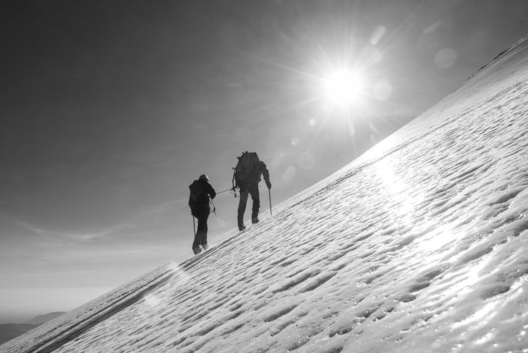 People walking on snowcapped mountain against sky during winter