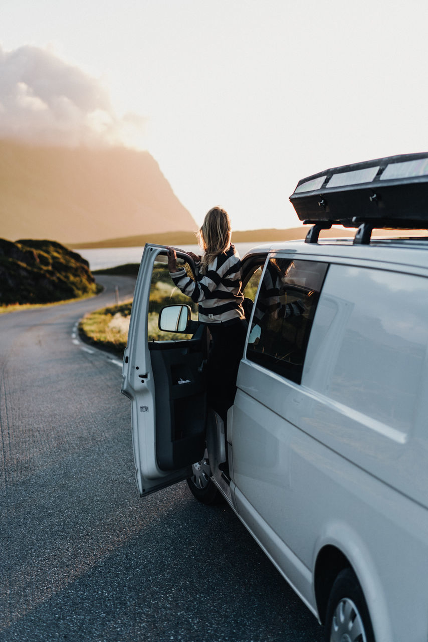 REAR VIEW OF WOMAN STANDING BY CAR ON MOUNTAIN
