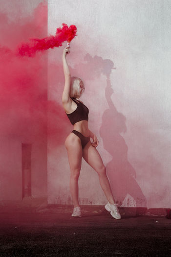 Full length of woman standing against pink wall