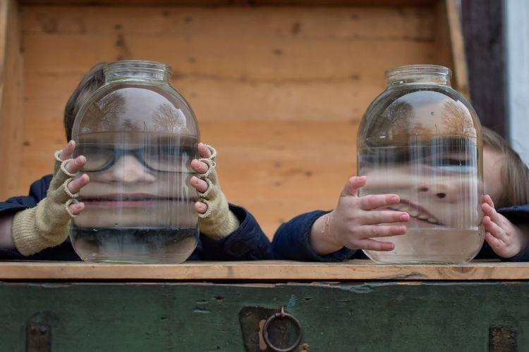 Siblings In Front Of Jars On Table