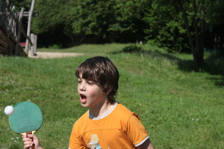 Teenage boy screaming while playing table tennis in park