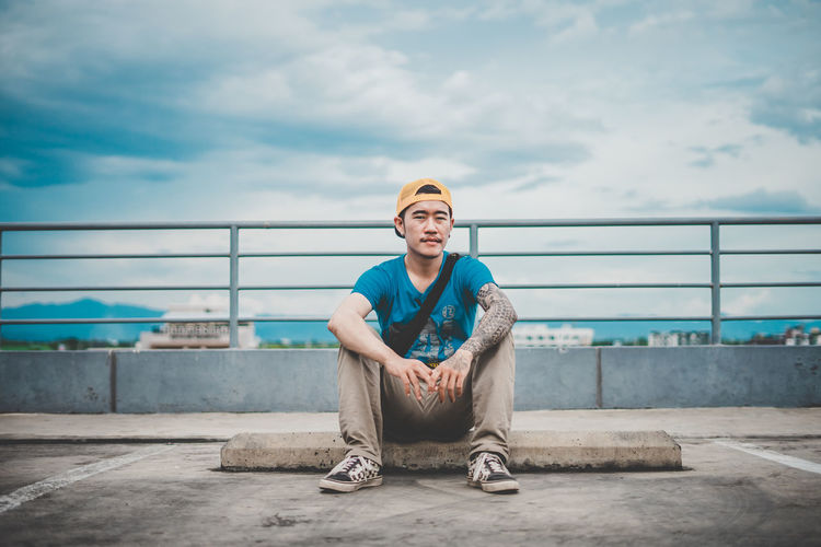 Portrait of young man sitting on street in city against sky