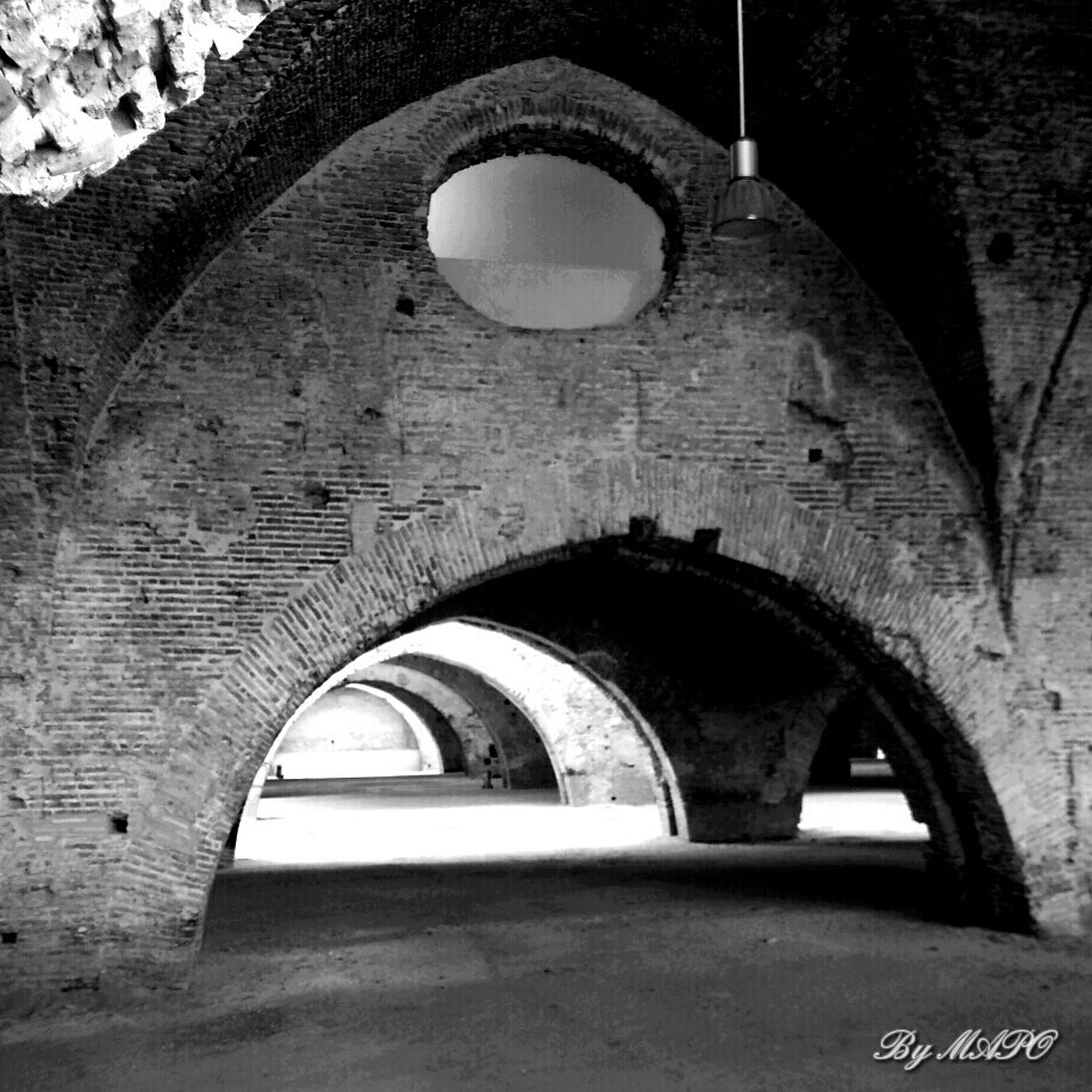 arch, architecture, built structure, building exterior, brick wall, circle, wall - building feature, wall, no people, stone wall, arched, old, day, archway, window, building, outdoors, low angle view, hole