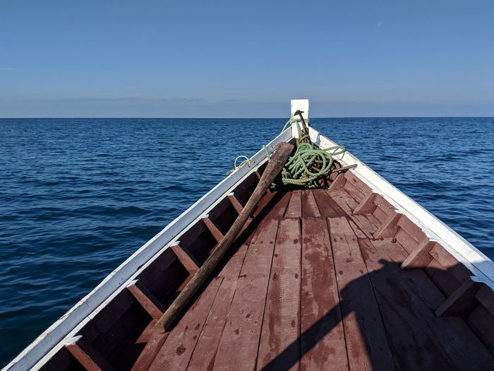 Wooden boat riding over sea against blue sky