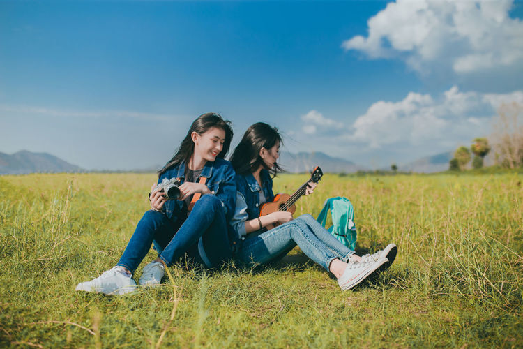 Friendship of Asian teenager women resting outdoor with camera and ukulele her playing music relax. Two People Sitting Togetherness Grass Plant Women Young Women Casual Clothing Sky Field Nature Leisure Activity Full Length Adult Young Adult Land Bonding Friendship Real People Lifestyles Couple - Relationship Positive Emotion Jeans Outdoors