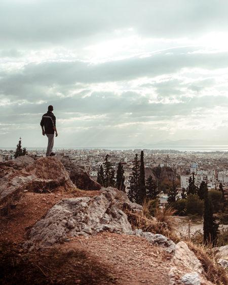 Man standing on rock against sky