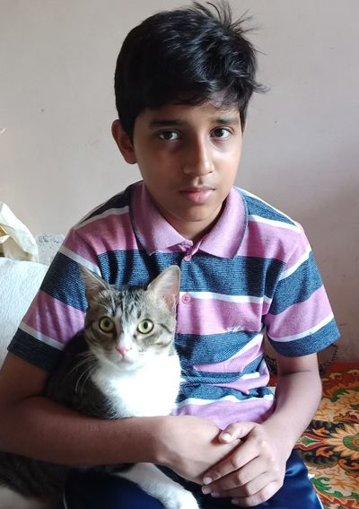 Portrait Of Boy Sitting With Cat On Bed At Home