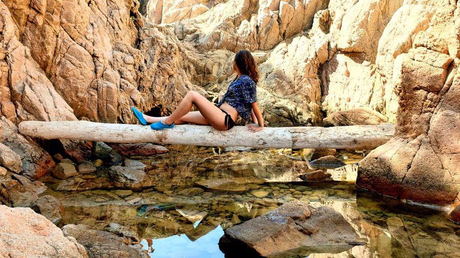 Side view of teenage girl sitting on log amidst rocks