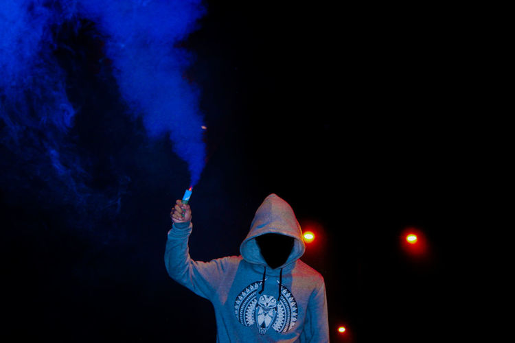 Person with smoke flare standing at night