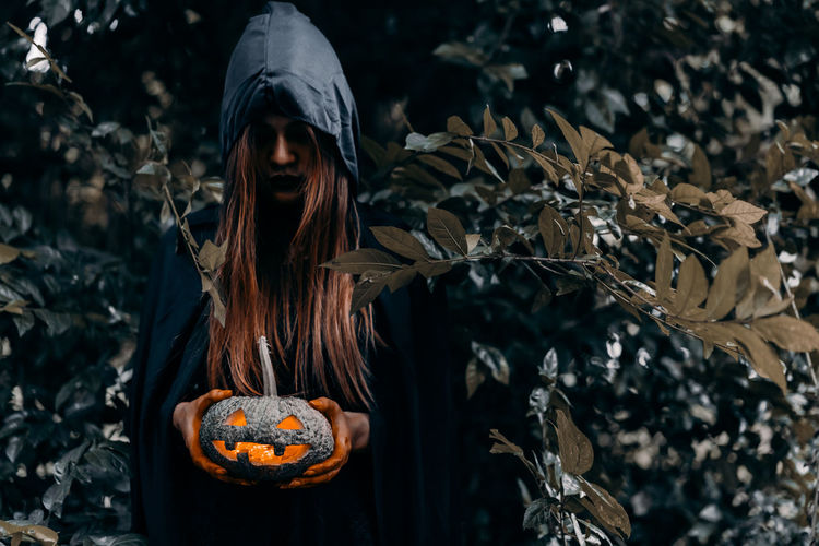 Young woman holding jack o lantern at forest during halloween