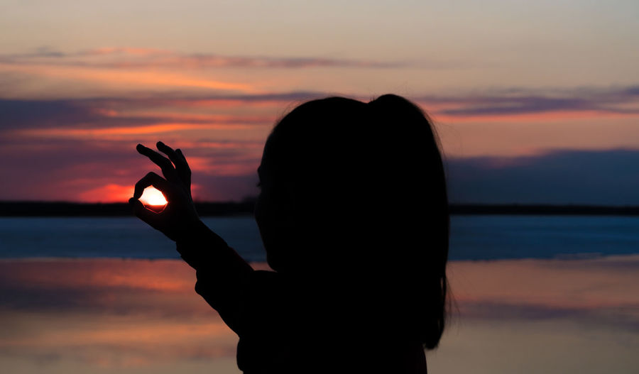 Silhouette woman showing ok sign against sky during sunset