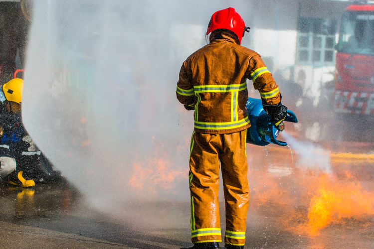 Rear view of firefighter extinguishing fire