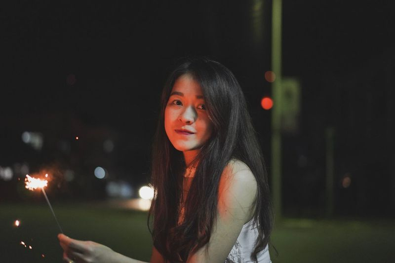 Portrait of beautiful woman holding sparkler at night
