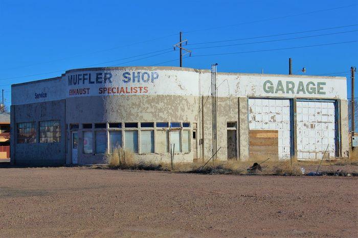 Abandoned muffler shop in Holbrook, Arizona. Abandoned Abandoned Buildings Architecture Arizona Blue Sky Boarded Up Broken Glass Decrepit Faded Fading Paint Garage Holbrook Muffler Shop Retro Route 66 Vintage Weathered