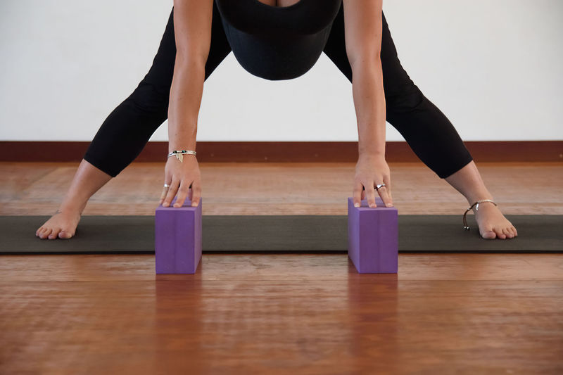 Low Section Of Pregnant Woman Exercising On Hardwood Floor