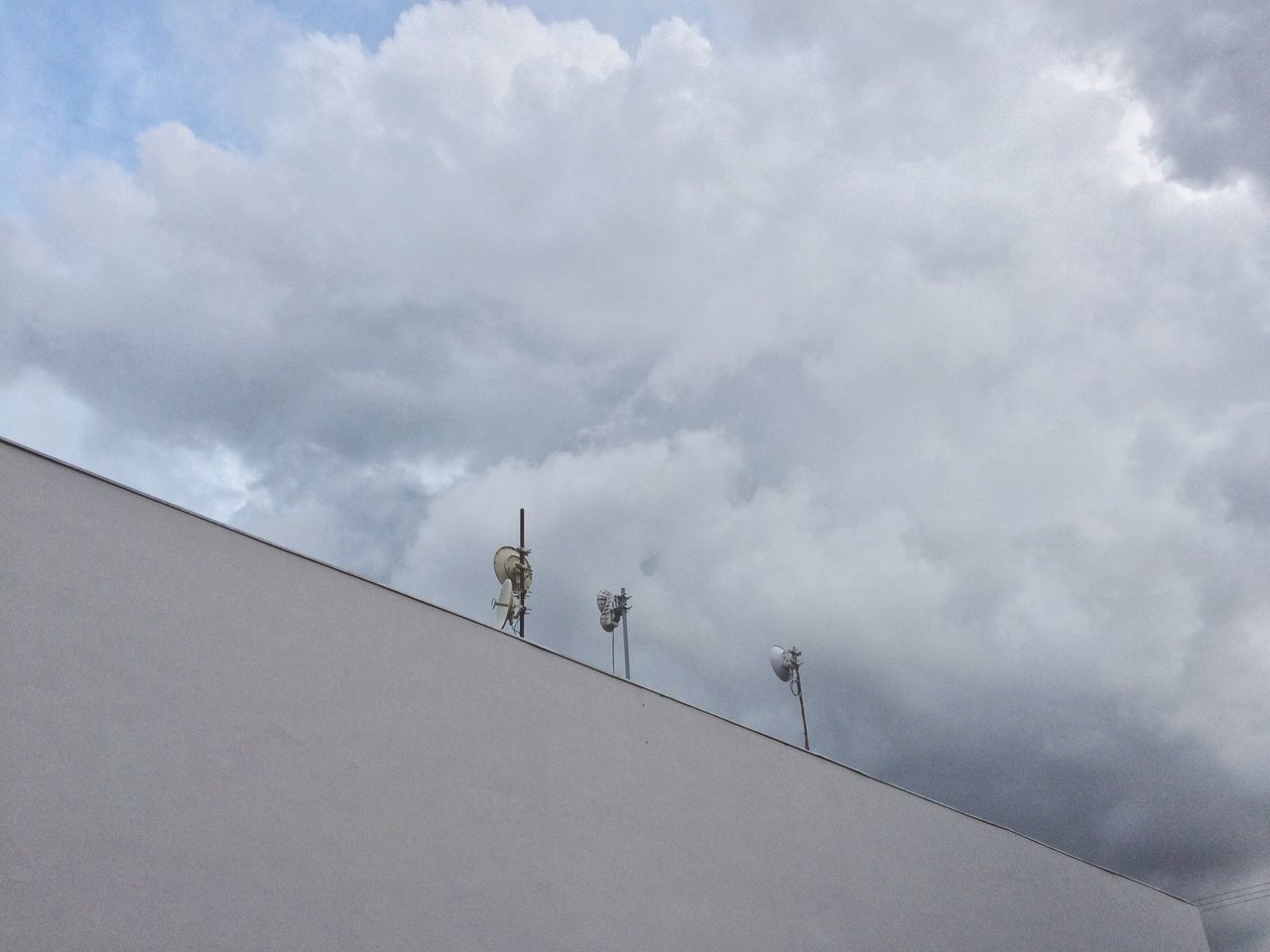 LOW ANGLE VIEW OF LIZARD ON WALL AGAINST SKY