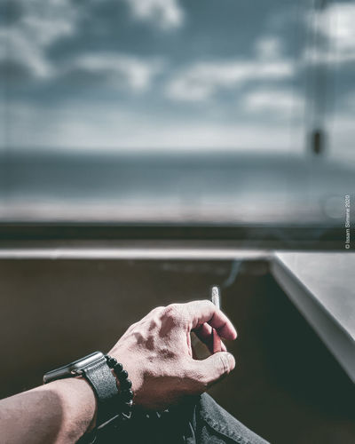 Cropped hand of man holding cigarette