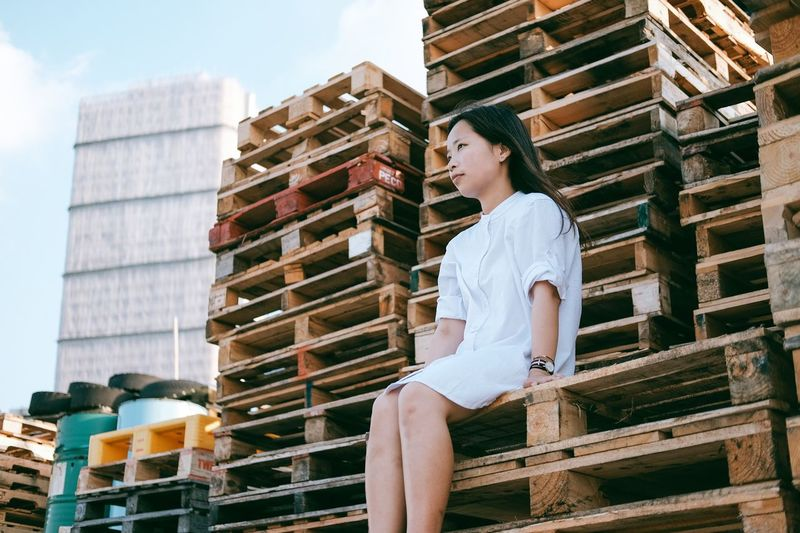 Full length of woman sitting by stack against sky