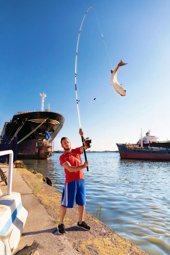 A driving boy fishing tear without bait. On the dock of an industrial harbor the fisherman, with his fishing pole, pulls out of the water a big mullet fish. Blue Casual Clothing Day Enjoyment Fisherman Fishing Lifestyles Mullet Outdoors Sky Sport Tourism Water Young Men