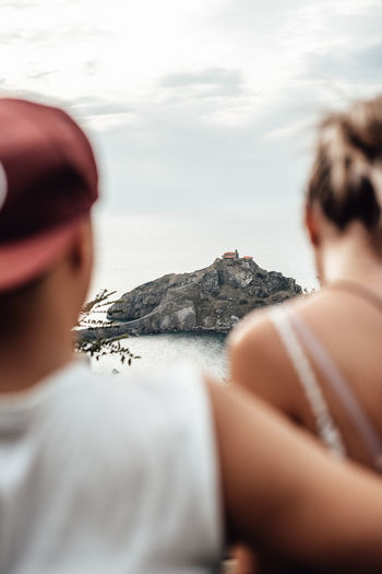 Rear view of couple sitting against rock mountain in sea