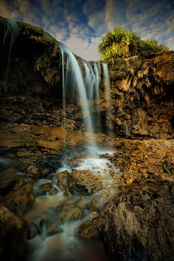 Low angle view of waterfall amidst rock formation