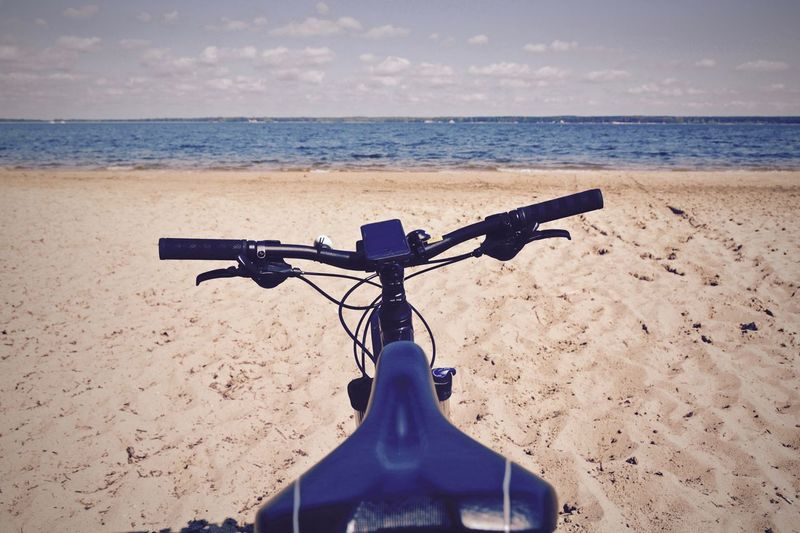 Bicycle at beach against sky