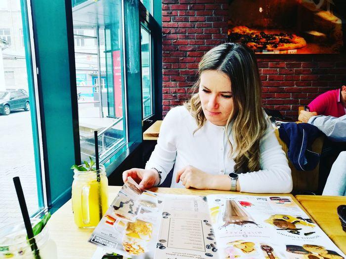 Young woman reading menu at restaurant