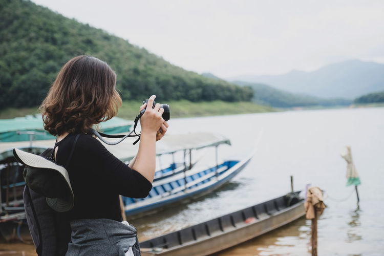 Rear view of woman photographing in lake