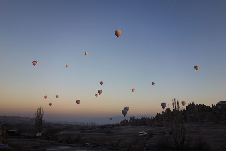 Hot air balloons flying over landscape against clear sky at cappadocia