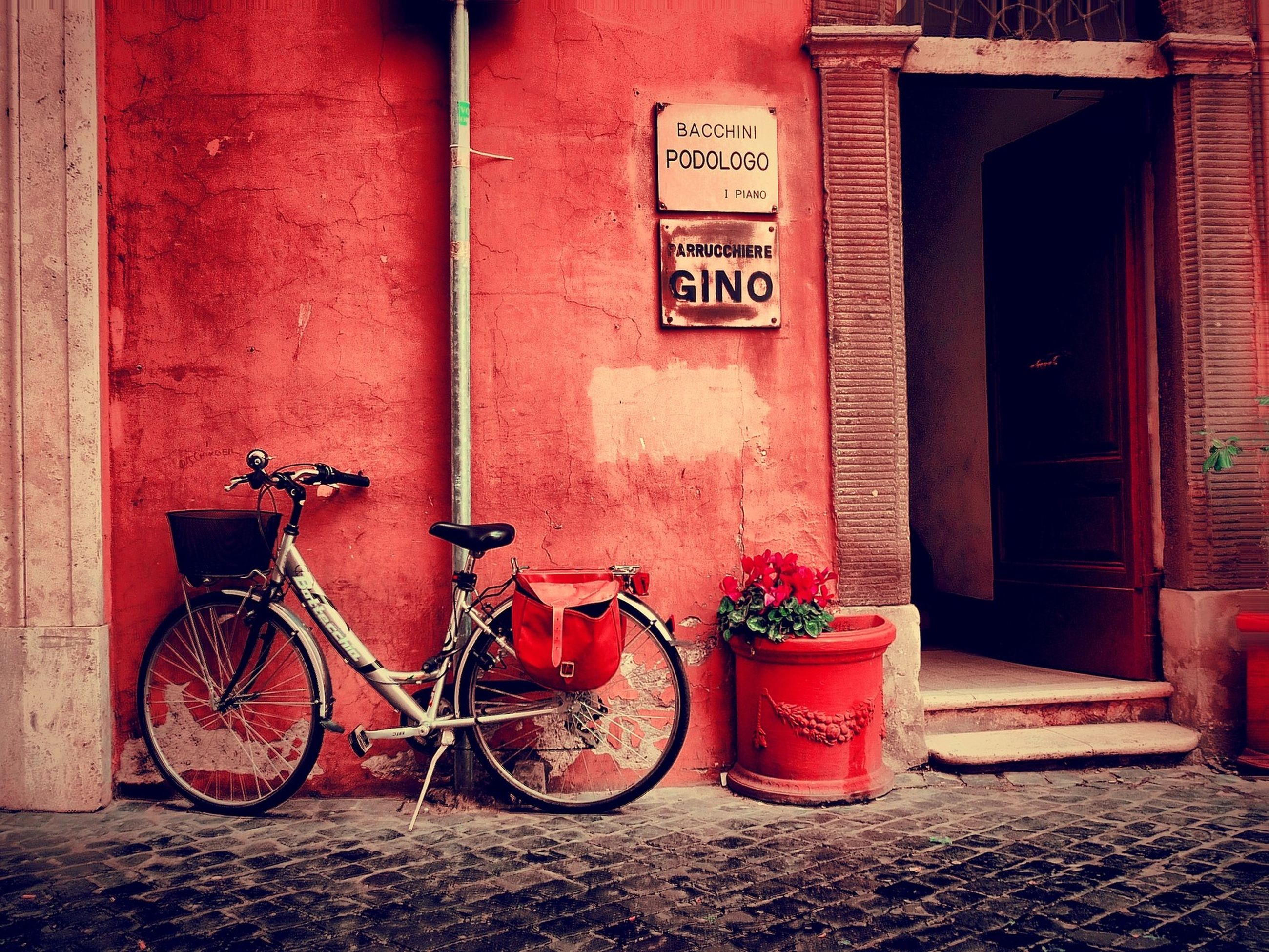 building exterior, red, architecture, built structure, bicycle, wall - building feature, house, parked, stationary, transportation, potted plant, wall, door, outdoors, parking, closed, day, brick wall, no people, flower