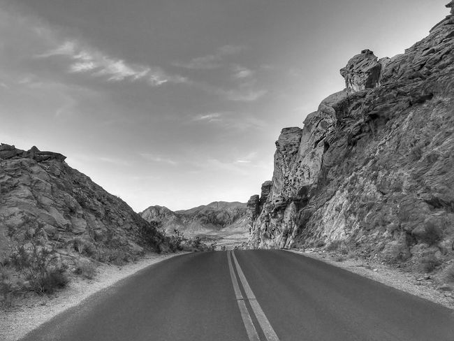A road through the sandstone hills in Valley of fire State Park EyeEmNewHere Black And White Road Road Marking The Way Forward Mountain Rock - Object Rock Formation Nature No People White Line Landscape Tranquility Beauty In Nature Outdoors Mountain Range Sky Tranquil Scene Scenics Physical Geography Transportation Day