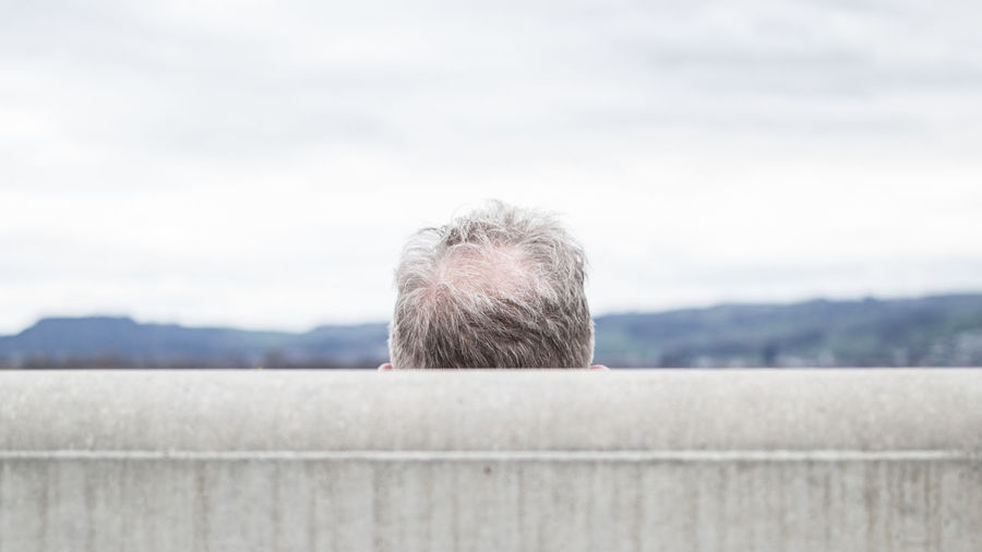 Cropped image of aged man against sky
