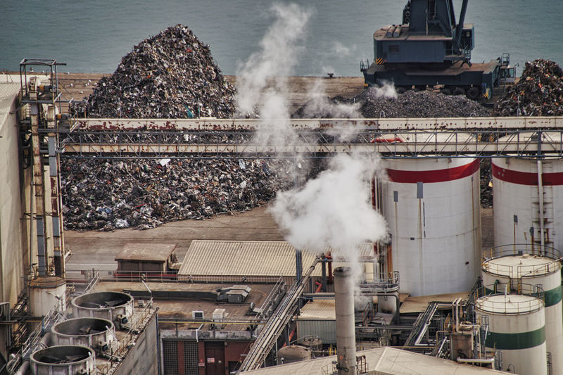High angle view of smoke emitting from factory at recycling center at harbor, barcelona