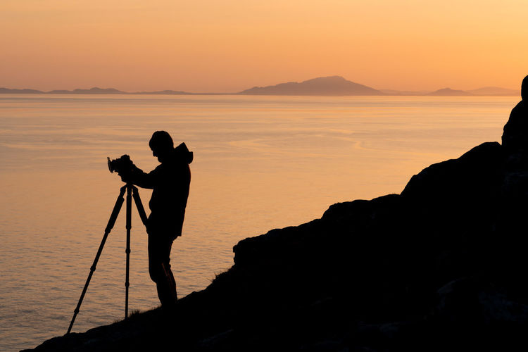 Silhouette Activity Beauty In Nature Camera - Photographic Equipment Digital Camera Island Leisure Activity Men One Person Outdoors Photographer Photography Themes Real People Rock Rock - Object Scenics - Nature Sea Silhouette Sky Sunset Tranquil Scene Tranquility Tripod Water The Great Outdoors - 2018 EyeEm Awards The Photojournalist - 2018 EyeEm Awards The Traveler - 2018 EyeEm Awards The Portraitist - 2018 EyeEm Awards Capture Tomorrow