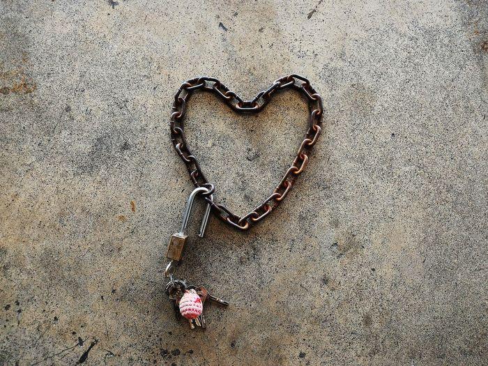 High angle view of heart shape chain on footpath