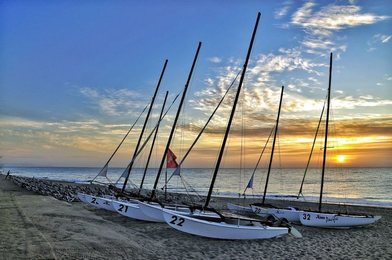 Boats on shore against calm sea at sunset