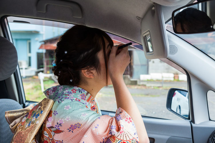 Woman Applying Make-Up In Car