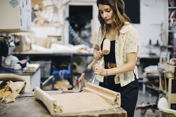 Female entrepreneur making furniture at workshop