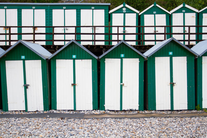 Rows of traditional, British green and white beach huts filling the frame on a pebble beach in Beer, Devon, UK. Architecture Beach Beach Hut Collection Beach Huts Beach Photography Beachphotography Beer British Culture Building Exterior Built Structure Changing Rooms Day Destination Devon Doors Holiday Holidays No People Outdoors Pebble Beach Rows Of Things Traditional Travel Uk Vacation