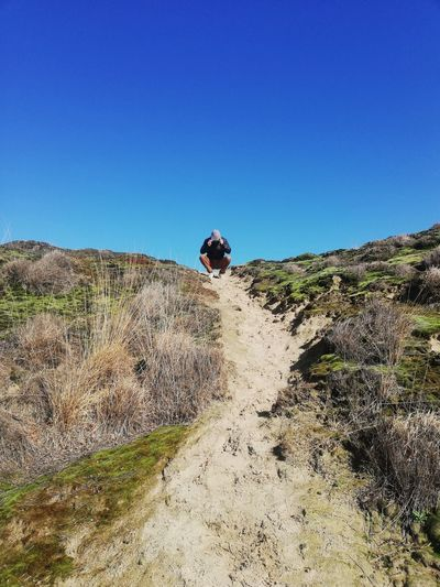 Man riding bicycle on mountain against clear blue sky