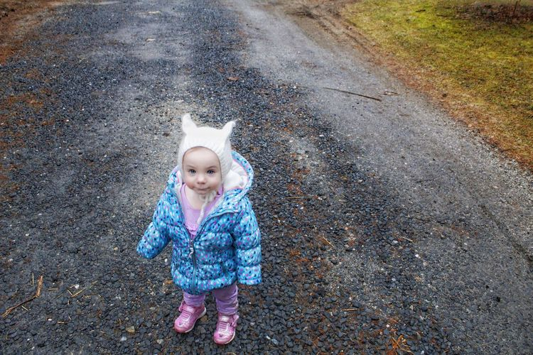 High angle portrait of cute baby girl standing on road