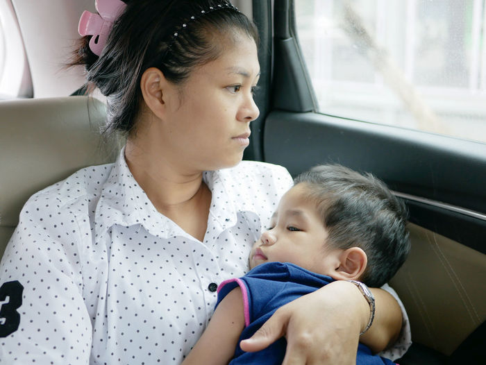 Mother with cute son sitting in car