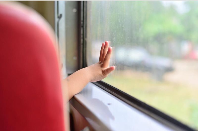 Cropped image of hand against train window